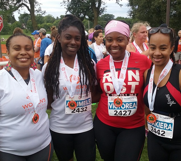 four women with race medals at ywca women's triathlon