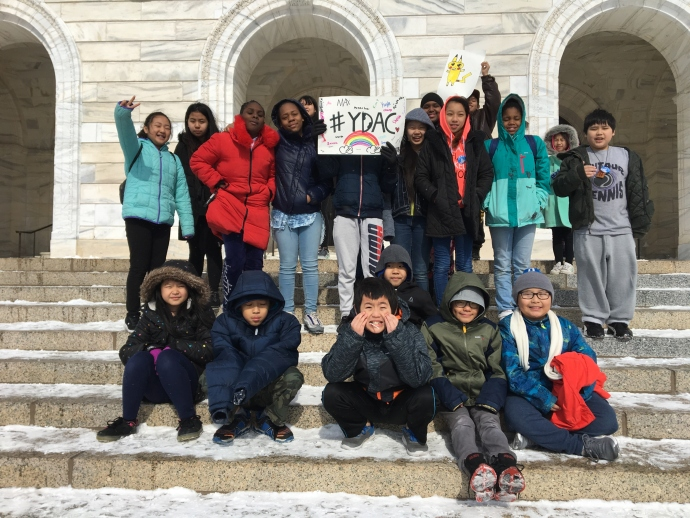 A group of YWCA youth both sit and stand on the Capitol steps with a sign that read #YDAC