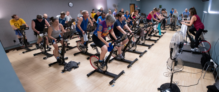 a packed Indoor Cycling Class at YWCA with participants on their bikes