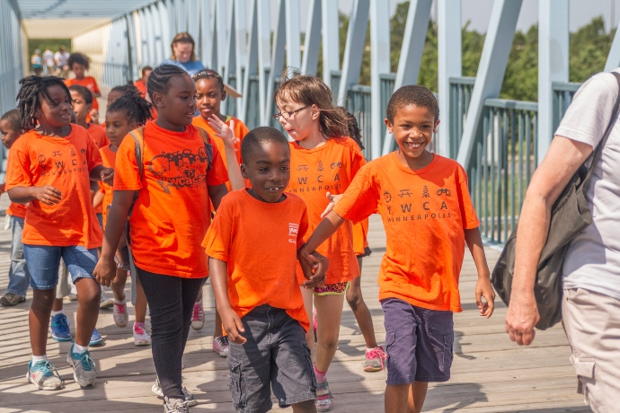 a group of children in orange shirts walk together across a bridge on a sunny day