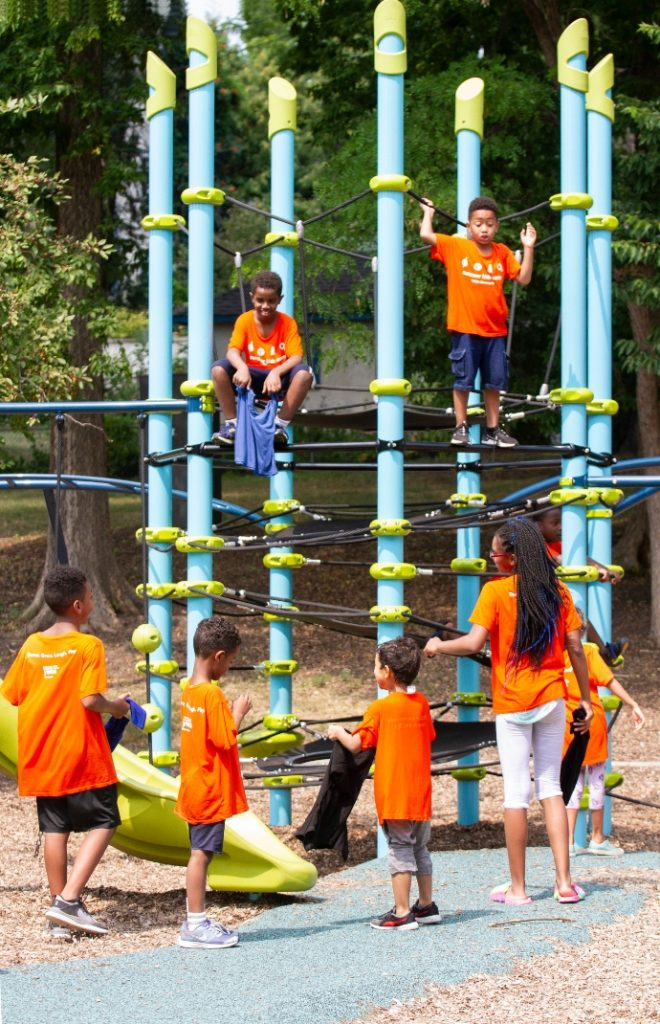 children in orange shirt climb a giant play structure in a city park