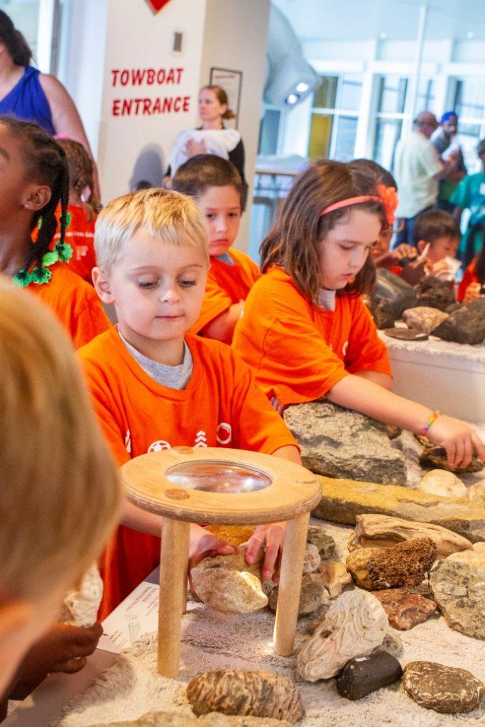 children in orange shirts examine different types of rocks under a magnifier