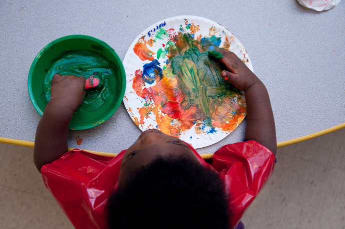 child at a table plays with multiple color paints