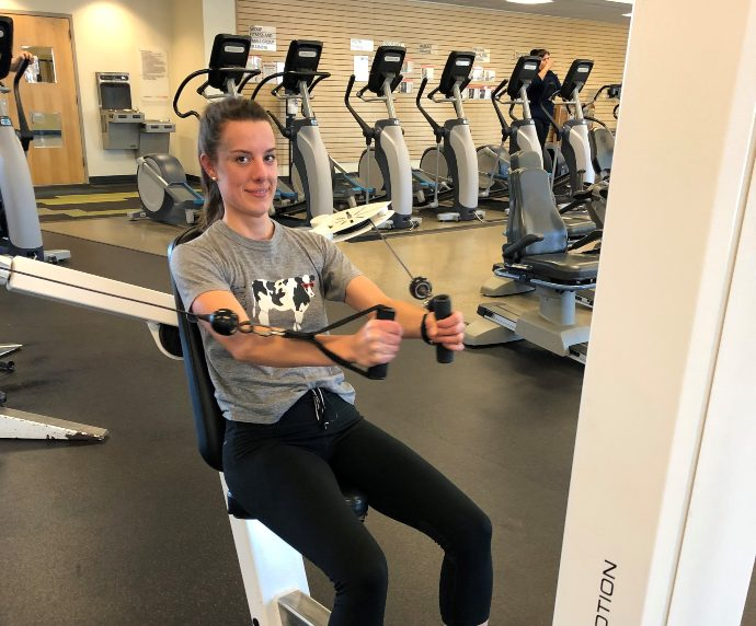 fitness member on a weight machine at the gym