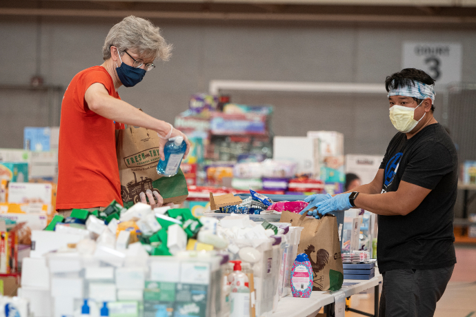 Two volunteers organize items on a table with supplies at YWCA Midtown