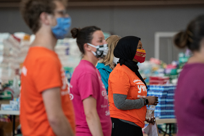 volunteers listen to safety and role instructions at YWCA distribution center